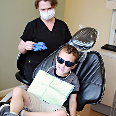 A Charlottesville dentistry team member with a young patient in the chair
