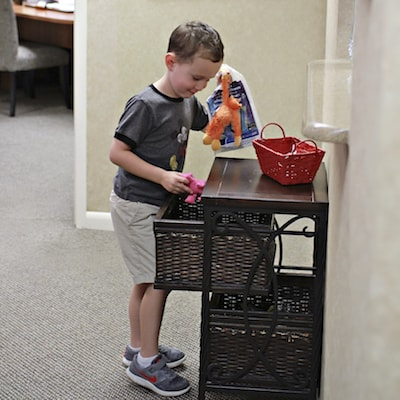 Charlottesville Family Dentistry is designed for kids as shown by this child looking through the toys