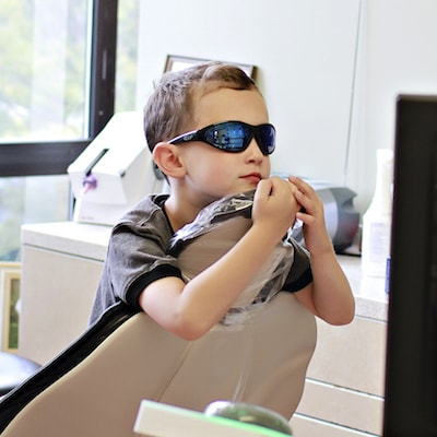 Charlottesville Family Dentistry is designed to alleviate anxiety, even in kids. This child is wearing glasses and is ready for care.